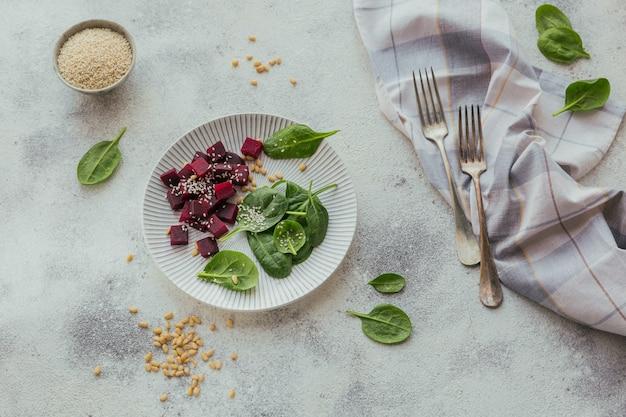 Petit-déjeuner sain avec de la betterave bouillie, des pousses d'épinards, des pignons de pin et des graines de sésame sur une surface blanche