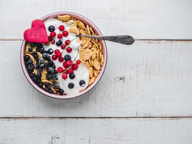 Petit-déjeuner sain. biscuits aux céréales, cornflakes, yaourt et baies fraîches