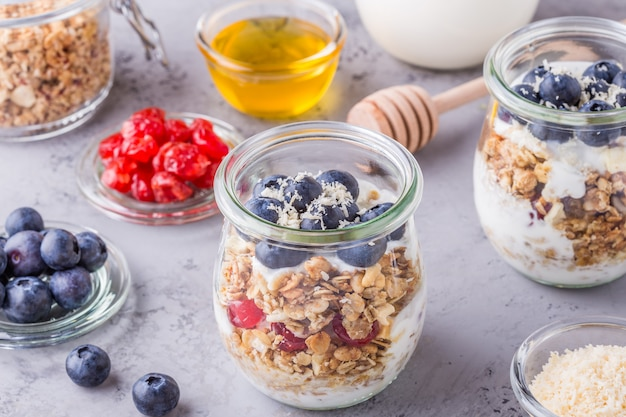 Petit-déjeuner sain - bocaux en verre de flocons d'avoine avec fruits frais, yogourt et miel