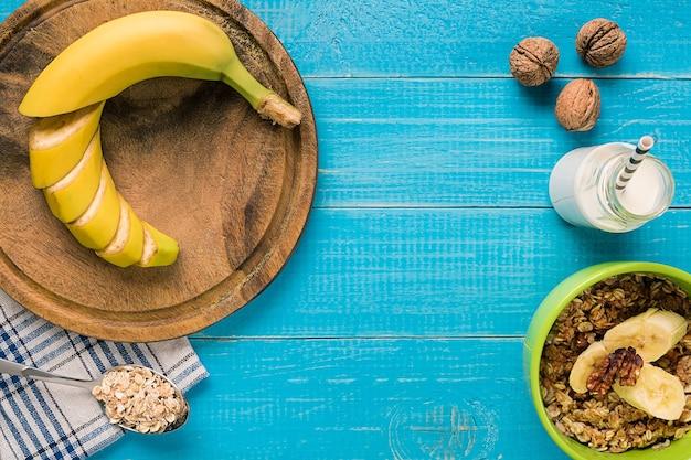 Petit-déjeuner sain avec bol de flocons d'avoine faits maison avec fruits et lait sur fond de bois rustique. nature morte. espace de copie