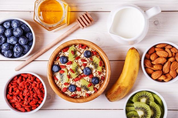 Petit-déjeuner sain - bol de flocons d'avoine avec fruits frais, amande et miel