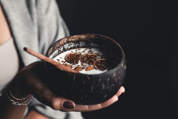Petit-déjeuner sain. ãƒâƒã'âƒãƒâ'ã'â ãƒâƒã'â'ãƒâ'ã'â¡ bol de noix de coco dans les mains d'une fille avec du yaourt et des figues. nourriture saine. veganisme.