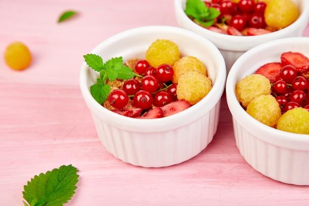 Petit déjeuner sain sur des bols blancs. granola, muesli ou céréale fraîche aux baies