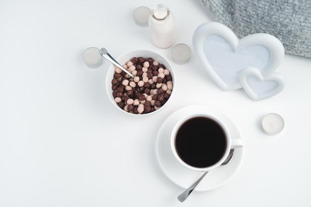 Petit-déjeuner sain avec un cadre avec des coeurs et des bougies sur blanc