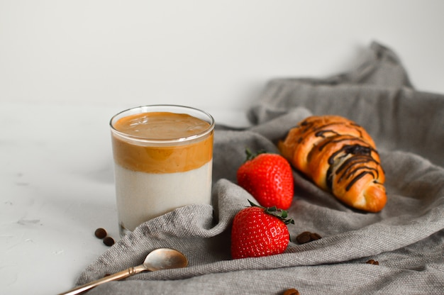 Petit-déjeuner sain: café froid dalgona, croissant et fraises sur blanc