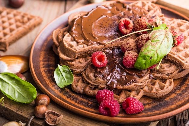 Petit-déjeuner sain avec des coeurs de gaufres chaudes fraîches, des crêpes à la crème au chocolat et à la framboise