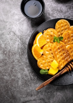 Petit-déjeuner sain avec des coeurs de gaufres chaudes fraîches, des fleurs de crêpes au miel de baies et des fruits exotiques sur une surface grise, vue de dessus, pose à plat. concept alimentaire