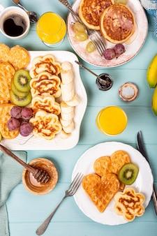 Petit-déjeuner sain avec coeurs de gaufres chaudes fraîches, fleurs de crêpes avec confiture de baies et fruits sur une surface turquoise, vue de dessus, pose à plat. concept alimentaire