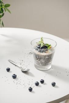 Petit-déjeuner sain ou collation du matin avec du pudding à la vanille aux graines de chia et des baies sur fond de bois, nourriture végétarienne, régime alimentaire et concept de santé