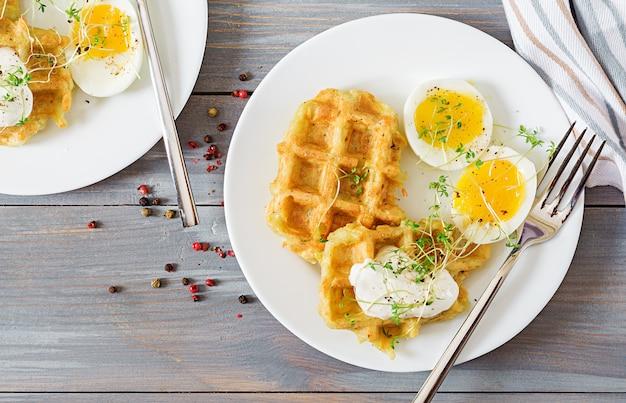 Petit-déjeuner sain ou collation. gaufres de pomme de terre et œuf à la coque sur une table en bois gris. vue de dessus. mise à plat