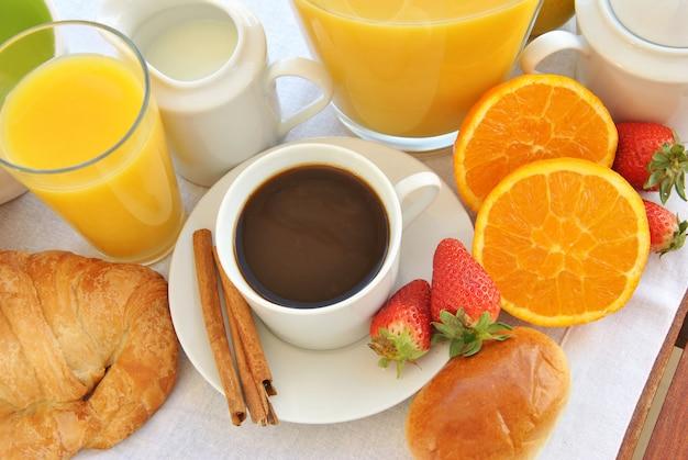 Petit-déjeuner sain composé de café, jus de fruits, fruits et croissant