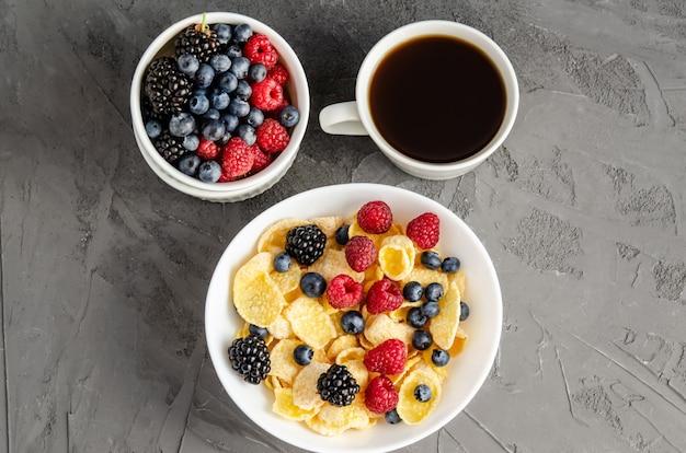 Petit-déjeuner sain avec des cornflakes dans une assiette blanche, des baies et du café