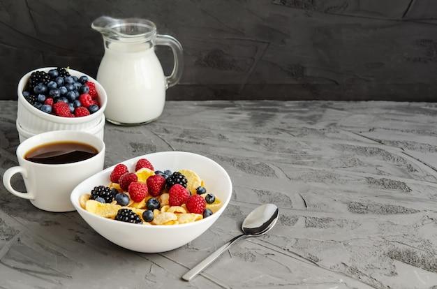 Petit-déjeuner sain avec des cornflakes dans une assiette blanche, des baies, du lait et du café