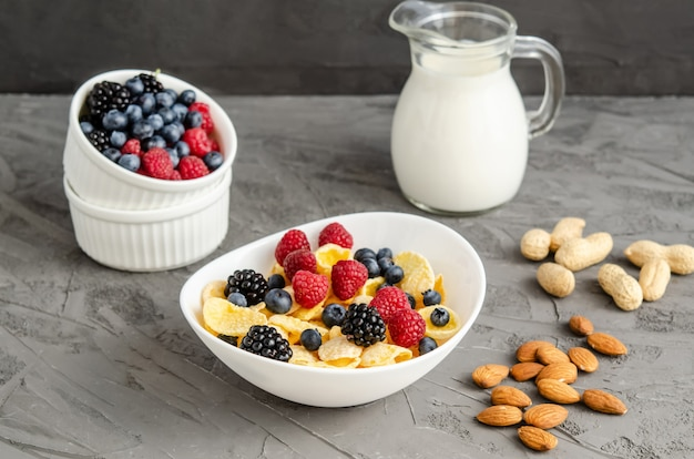 Petit-déjeuner sain avec des cornflakes dans une assiette blanche, des baies, du lait et des noix