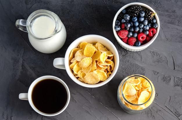 Petit-déjeuner sain avec des cornflakes dans une tasse blanche, des baies, du lait et du café