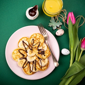 Petit-déjeuner sain avec des crêpes chaudes fraîches avec des bananes et du chocolat sur une surface verte, vue du dessus