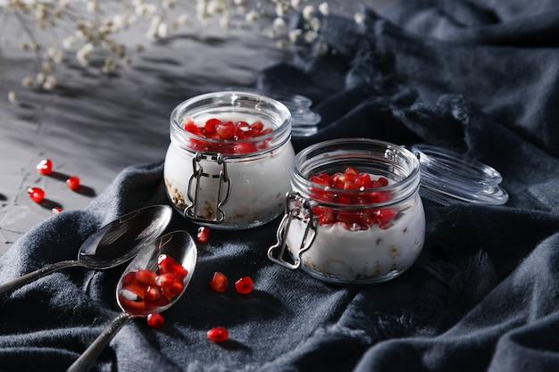 Un petit-déjeuner sain dans des bocaux de yaourt, d'avoine et de grenade