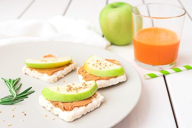 Petit-déjeuner sain avec du beurre d'arachide et des sandwichs aux pommes sur des gâteaux de riz jus de carotte et pomme sur fond en bois blanc