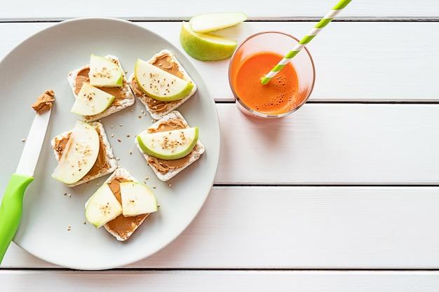 Petit-déjeuner sain avec du beurre d'arachide et des sandwichs aux pommes sur des gâteaux de riz jus de carotte vue de dessus sur fond en bois blanc copy space