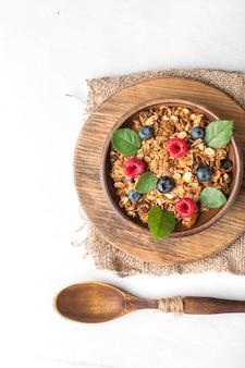 Petit-déjeuner sain avec du granola et des baies sur fond blanc