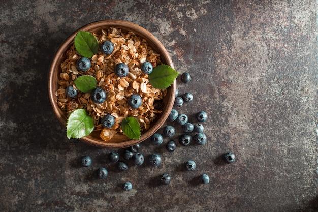 Petit-déjeuner sain avec du granola et des baies sur fond sombre