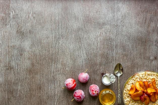 Petit-déjeuner sain avec de la farine d'avoine dans un bol en verre, des prunes, du miel et de la crème sur fond de bois foncé. vue de dessus. espace de copie. nature morte. mise à plat