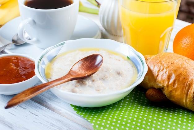 Petit-déjeuner sain avec des flocons d'avoine avec du beurre, des croissants et du café