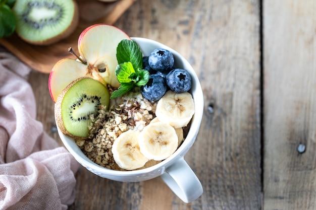 Petit-déjeuner sain, flocons d'avoine ou granola aux bleuets, pomme, kiwi et menthe sur un fond en bois rustique. fermer. espace copie