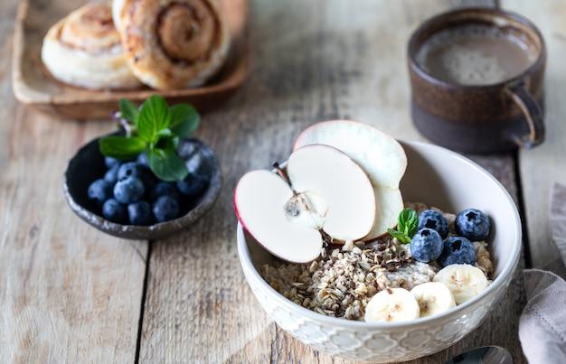 Petit-déjeuner sain, flocons d'avoine ou granola aux bleuets, pomme, noix et menthe sur un fond en bois rustique