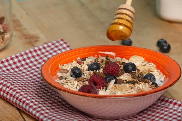 Petit-déjeuner sain avec flocons d'avoine, noix, miel, bleuets et framboises