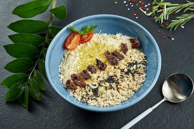 Petit-déjeuner sain: flocons d'avoine avec tomates séchées au soleil, parmesan et beurre dans un bol bleu sur une surface noire