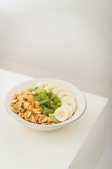 Petit-déjeuner sain avec des flocons de son riches en fibres, du kiwi et de la banane