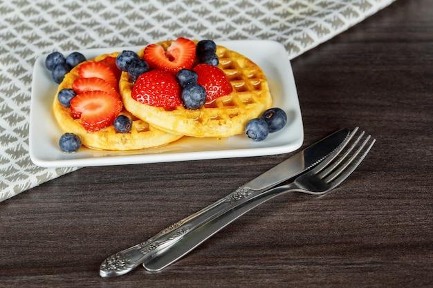 Petit-déjeuner sain: gaufres belges à la crème sure, fraises, framboises, myrtilles