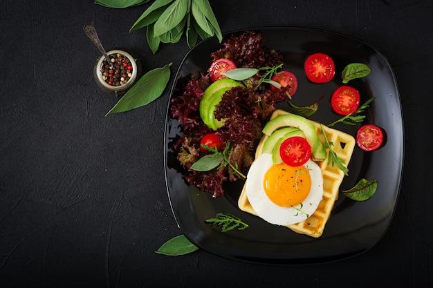 Petit-déjeuner sain - gaufres, œufs, avocat, tomates et herbes. mise à plat. vue de dessus