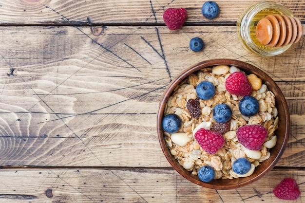 Petit-déjeuner sain. granola fraîche, muesli avec du yogourt et des baies sur une surface en bois