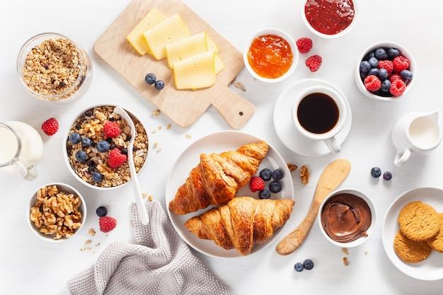 Petit-déjeuner sain avec granola, petits fruits, noix, croissant, confiture, pâte à tartiner au chocolat et café. vue de dessus