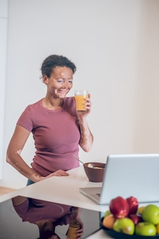 Petit-déjeuner sain. jeune femme à la peau foncée prenant son petit déjeuner à la maison et buvant du jus d'orange