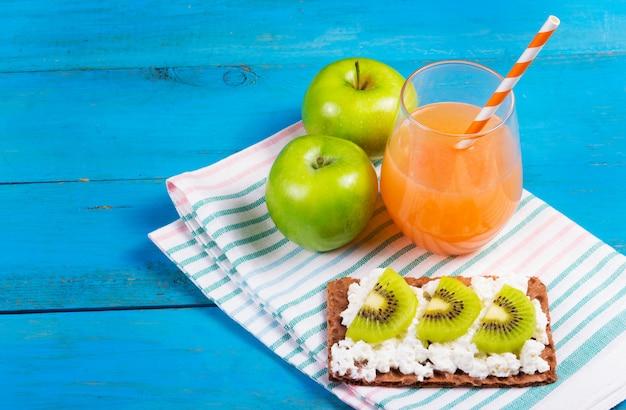 Petit-déjeuner sain, jus de pamplemousse, pomme verte et pain grillé avec du fromage et des tranches de kiwi.