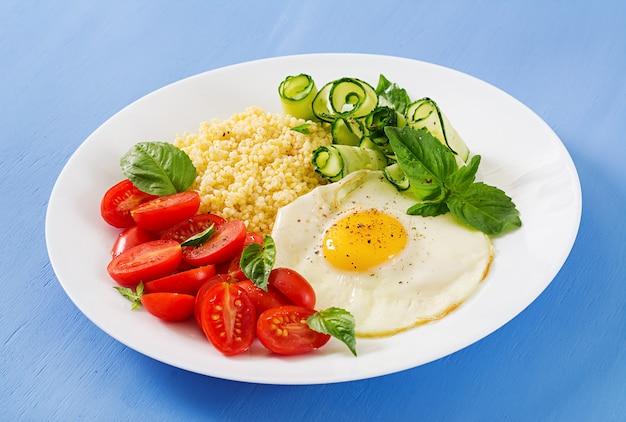 Petit-déjeuner sain. menu diététique. bouillie de millet et tomates, salade de concombre et œufs au plat.