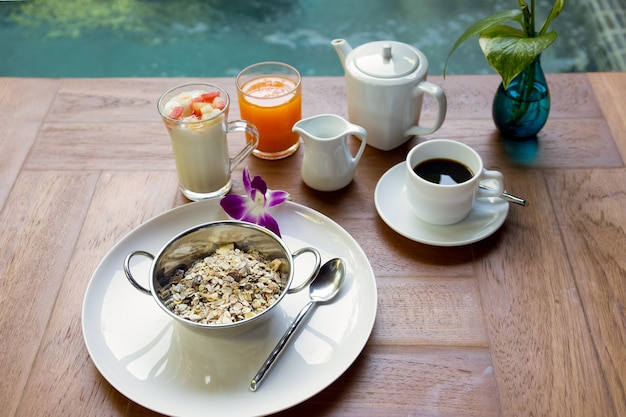Petit-déjeuner sain muesli alimentaire variée, yaourt aux fruits, café, jus d'orange.