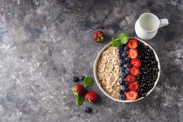 Petit-déjeuner sain, muesli aux groseilles, myrtilles et fraises en bawl sur un espace sombre