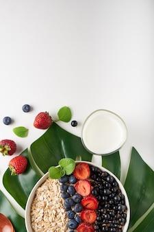 Petit-déjeuner sain, muesli aux groseilles, myrtilles et fraises servi en bawl sur un espace lumineux
