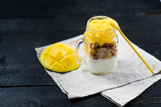 Petit déjeuner sain muesli et yaourt avec smoothie à la mangue dans des bocaux en verre.