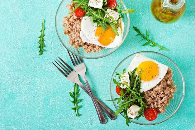Petit-déjeuner sain avec oeuf, fromage feta, roquette, tomates et bouillie de sarrasin sur fond clair. nutrition adéquat. menu diététique. mise à plat. vue de dessus