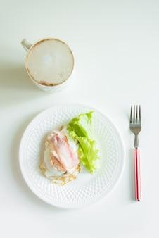 Petit-déjeuner sain, œufs au plat, bacon, salade verte et café