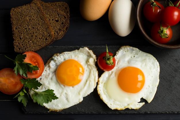 Petit-déjeuner sain. œufs frits, légumes et pain. vue de dessus.