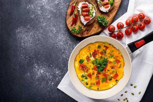 Petit-déjeuner sain, omelette aux œufs farcis aux légumes et tomates cerises et sandwichs