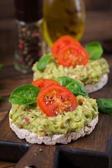 Petit-déjeuner sain. pain croustillant sandwich avec guacamole et tomates sur une table en bois.