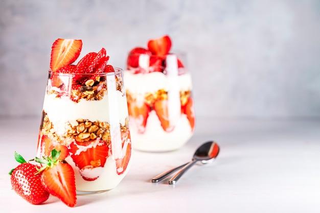Petit-déjeuner sain de parfaits aux fraises à base de yaourt aux fraises fraîches et de muesli dans des verres