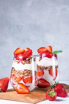 Petit-déjeuner sain de parfaits aux fraises à base de yaourt frais et de muesli dans des verres